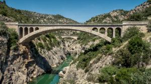 Flussaufwärts der Pont du Diable über den Fluss Hérault. Die zweibogige Steinbrücke wurde im 11. Jahrhundert erbaut und war Teil des Pilgerwegs nach Santiago de Compostela.  Weltkulturerbe der UNESCO.  Monument historique.