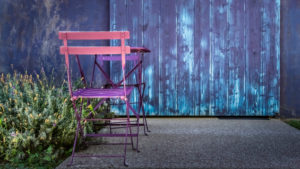 Table and chairs in front of a blue wall in Assignan in summer