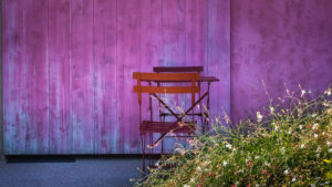 Table and chairs in front of a purple wall in Assignan in summer