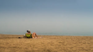Seated woman in fog in Narbonne Plage in summer
