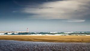 Leerer Strand und Leuchtturm in Port la Nouvelle im Sommer.