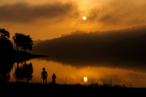 Germany, North Rhine-Westphalia, playing children on the lake in front of the morning sun