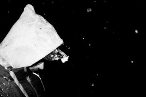Man with hood and snowflakes, sideways, close-up, at night