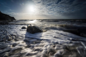 Baltic sea at evening light and long exposure, setting sun lights stones in the sea water