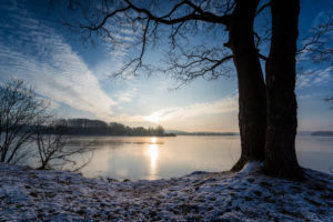 Sunrise over the lake in winter with drifting clouds