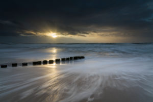 Baltic Sea in the evening light, long exposure, beach, sandstorm, blown groynes, moving clouds and rain showers with strong wind.