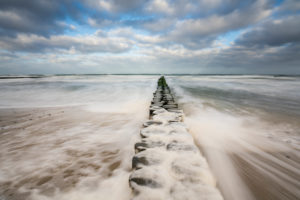 A beach on the Baltic Sea in winter, pulling waves, sea foam and groyne leading into the sea, long exposure