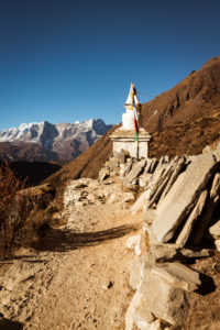 Temple on the way in the Khumbu valley, stone slabs in the foreground, mountains in the background