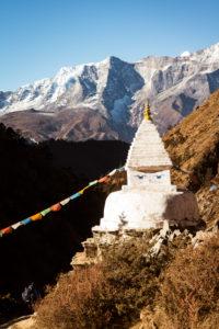 Tempel mit Gebetsfahnen, Gebirge im Hintergrund