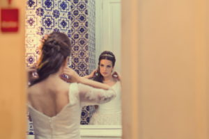view through the door, bride in front of mirror,