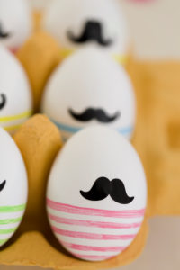 Easter eggs with moustache and stripes in the egg carton,