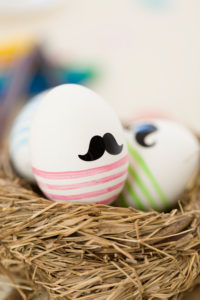 Easter nest, painted eggs with moustache and stripes