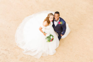 Wedding, newlyweds, young adults, diversity, love, sand, bird's eye view
