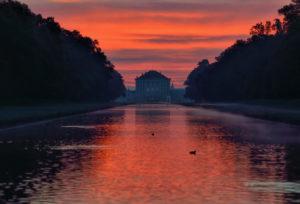 Deutschland, Bayern, vom Mittelkanal zu sehen das Schloss Nymphenburg  und Sonnenaufgang