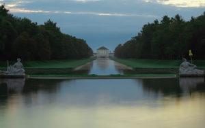 Deutschland, Bayern, Schloss Nymphenburg mit Parkanlage und Sonnenaufgang, zu sehen Symbol der Donau und Isar