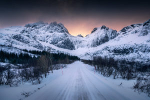 Norway, Lofoten, road in winter, sunset behind the mountains