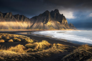 Vestrahorn mountains behind black beach in morning light, Iceland.