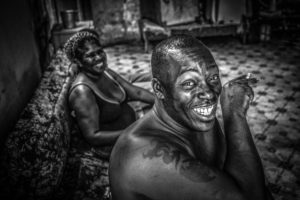 Cuba, Havanna, laughing couple sitting on the sofa, time for a cigarette,