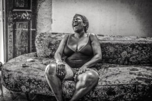 Cuba, Havanna, Woman sitting on sofa and laughing, Life can be funny,