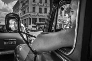 Cuba, Havanna, Man looks in the side mirror of his car, face, reflection,