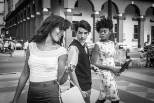Cuba, Havanna, pretty young woman crosses the street, man looks for her, woman with jealous glance