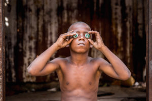 Cuba, Havanna, Boy holding bottle caps before his eyes, 'looking into the future',