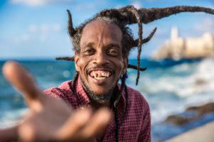 Cuba, Havanna, El Demonio, cheerful man with dreadlocks on the beach, gestures
