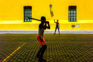 Cuba, Havanna, two boys playing Stick Ball in front of a yellow wall