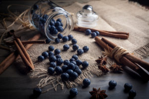 Blueberries and cinnamon sticks on jute cloth