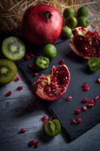 Granatapfel und Kiwis auf Schieferplatte