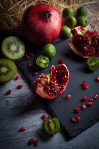 Pomegranate and kiwis on slate plate