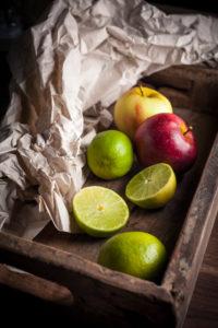 Äpfel und Limetten in Holzkiste