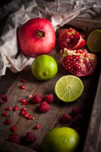 Granatapfel, Himbeeren und Limonen in Holzkiste