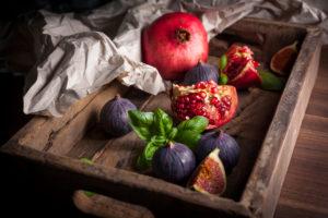 Granatapfel, Feigen und Basilikum in Holzkiste