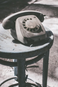 Dusty old telephone on stool