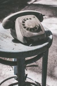 Staubiges altes Telefon auf Hocker