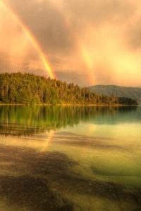 HDR Aufnahme eines doppelten Regenbogen über dem klaren Wasser des Walchensee.