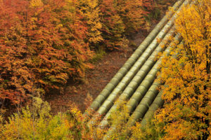 Conduits of the hydroelectric power plant Walchensee between autumnal trees.