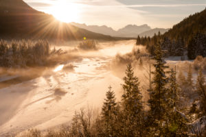 Back light of the setting sun in the Isar valley. In the foreground fog, the Isar with fresh snowfall and spruces. In the background the Zugspitze and Wetterstein Range.