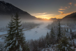 Sundown behind Wetterstein Range with Zugspitze. In the foreground the snow-covered Isar valley and spruces in the fog.