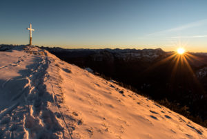 Evening sun at the summit of the Heimgarten, summit cross shines in the snow of the foreground footprints.