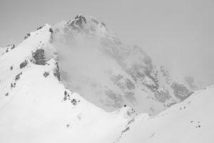 Eine kleine Gruppe Gämsen rechts unten im Bild gegen die Größe und Unwirtlichkeit bei Schlechtwetter im Winter an einem Berghang der Schöttelkarspitze an der Soierngruppe im Karwendel.