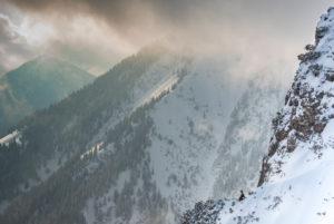 Gämse auf einem verschneiten Vorsprung unterhalb des Gipfels vom Herzogstand, während dramatischer Licht und Wetterstimmung.