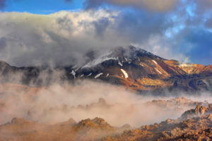Morning fog and light mood in the Oturere Valley, Tongariro national park, New Zealand. Clouds drag about cleft volcanic rock, with different grass, lichens and Lichen. In the background the Mount Ngauruhoe. The volcano plateau is sometimes known also as a level of Mordor.