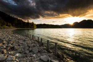 Wolkenstimmung während Sonnenuntergang am Walchensee in den bayrischen Voralpen, Uferböschung, Steine und Holzpfähle
