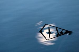 Spiegelung von Schilfhalmen und dem aufgehenden Mond im Wasser von einem kleinen See in den bayerischen Alpen bei Sonnenuntergang. Hoher Kontrast verstärkt die Strukturen.
