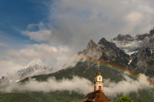 Rainbow over the church tower of Mittenwald in the Bavarian Karwendel. In the background the partly snow covered western Karwendel mountains.