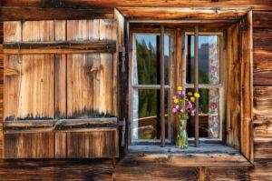 Detail auf der Gütenbergalm. Ein Wildblumenstrauß im Fenster der Holzhütte