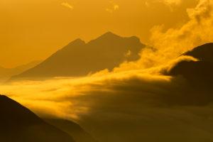 Hochnebel schwebt im goldenen Abendlicht über das Plumsjoch im Karwendel, gesehen vom Rofangebirge aus.