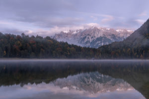 Evening mood with light fog at the Ferchensee near Mittenwald. In the background the Karwendel Mountains